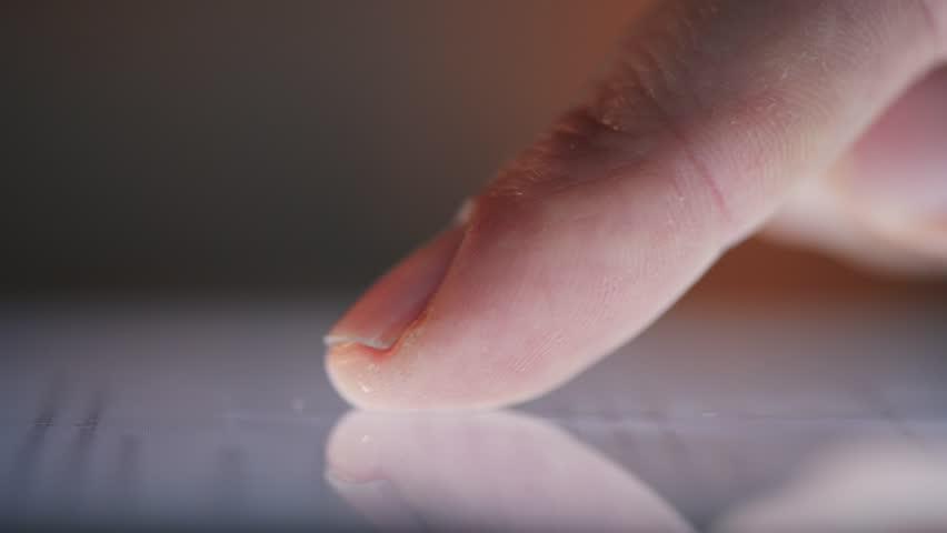 macro closeup finger touching tablet computer touchscreen
