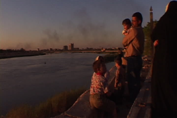 BAGHDAD, IRAQ - APRIL 29, 2003: Iraqi family looks out over the Tigris River at sunset.
