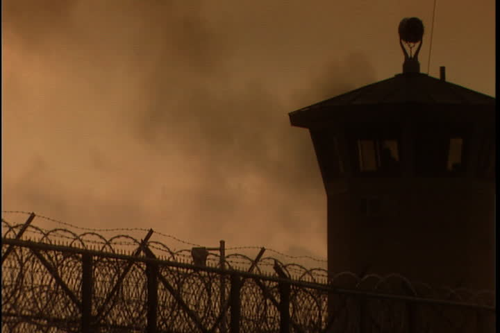 Silhouette of guard tower and barbed wire perimeter fence in morning mist and haze at Southern Ohio Correctional Facility in Lucasville, Ohio.