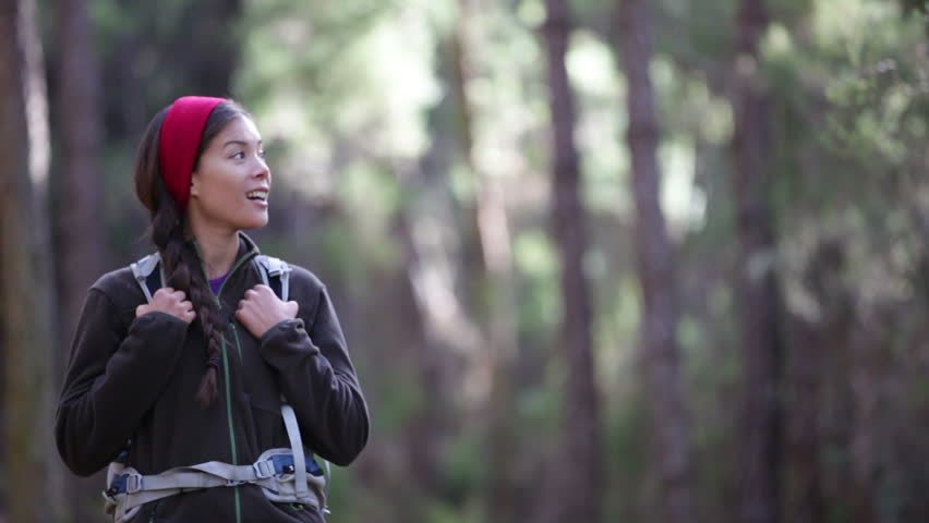 Hiker woman hiking in forest, stops and looks around. Smiling happy active female during hike in forest on Tenerife, Canary Islands, Spain. Sporty Asian female model.