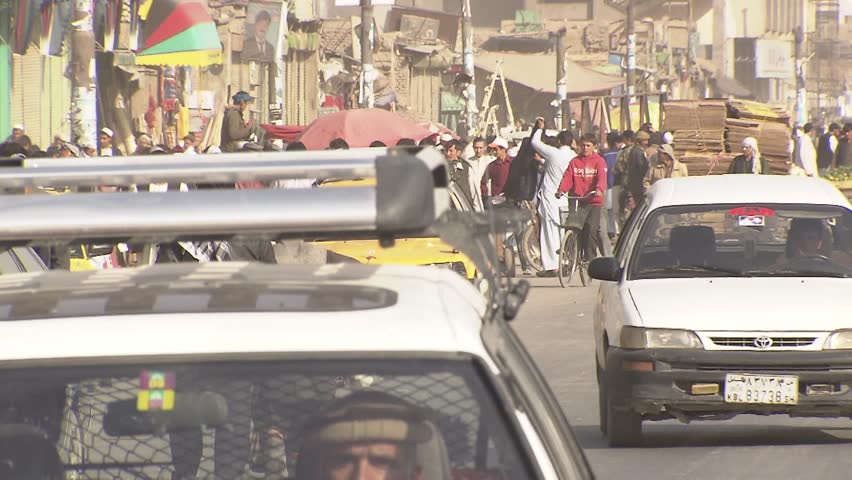 KABUL / AFGHANISTAN - November 15: Crowded street in front of market place. Unidentified people pass by. Drivers honk in city center of Kabul on November 15, 2011. - HD stock video clip