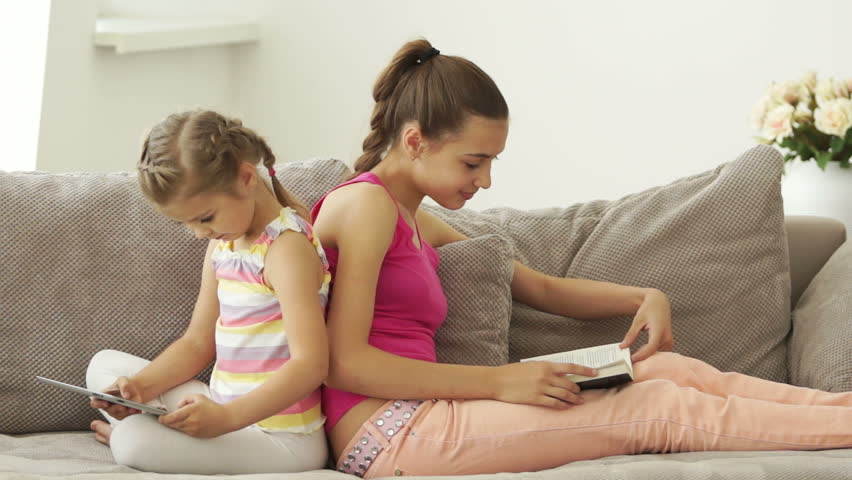 Two sisters sitting on the couch with a book and a tablet