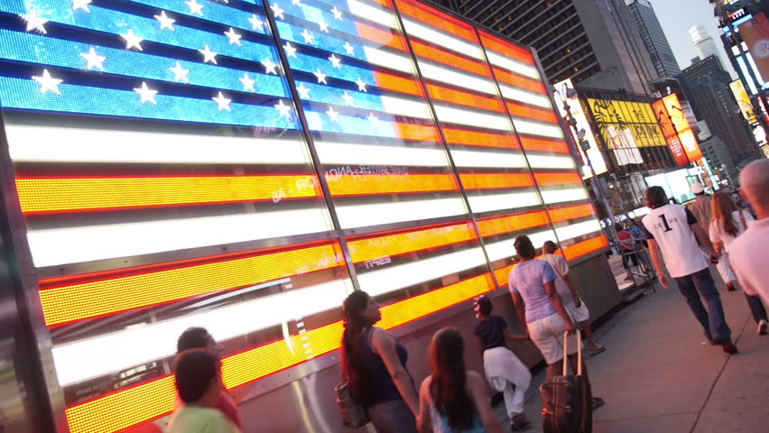 NEW YORK CITY, Circa June, 2013 - People pass the large neon American flag in
