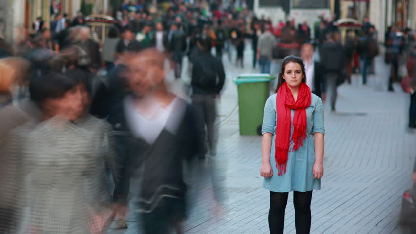 Young woman standing in busy city street, fast motion time lapse