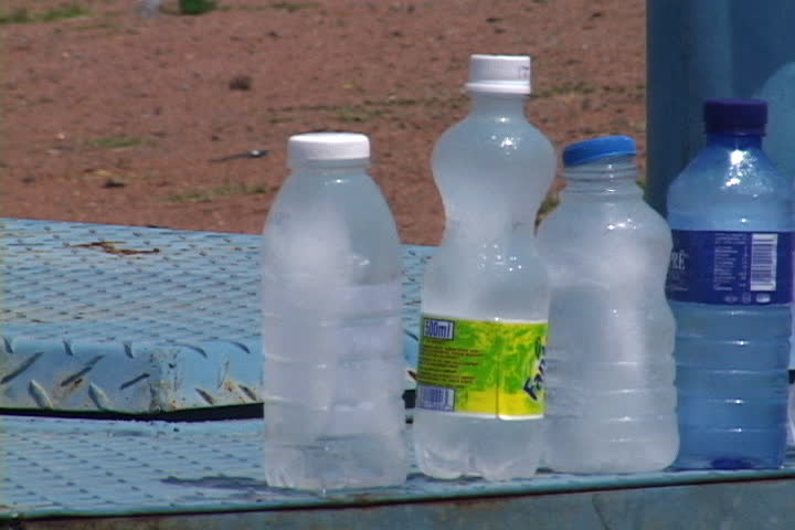 WINTERVELDT, SOUTH AFRICA - OCTOBER 01, 2005: Pan over bottles of water for sale at roadside stand, bottles have old beverage labels on them.
