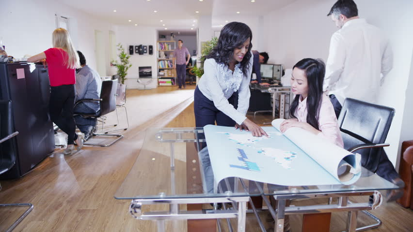 Two beautiful multi-ethnic businesswomen sitting in a light and modern open plan office and looking at a map of the world. They are discussing possibilities for future business ventures. Slow motion