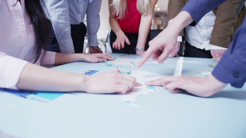 A business team of mixed ethnicity are working in a light and modern open plan office. They are looking at a map of the world and discussing possibilities for future business ventures. In slow motion.