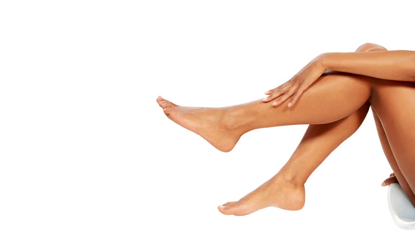 Beautiful female legs isolated over white background.Beauty and skin care concept. - HD stock footage clip