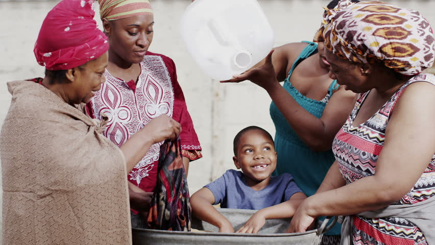 African family and community members of different generations work together to wash their clothes by hand. In slow motion. - HD stock video clip