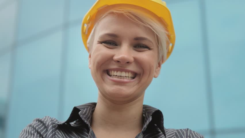 Young people at construction site, portrait of female architect with helmet smiling at camera. Sequence