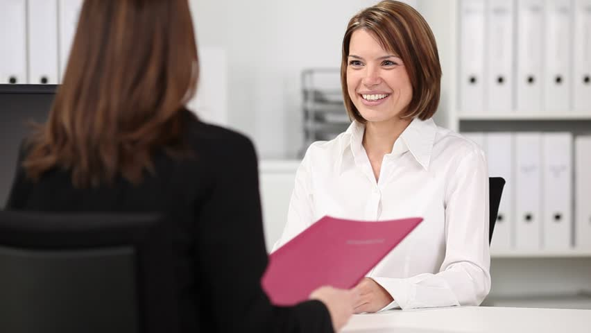 Happy young businesswoman shaking hands with candidate during an interview at desk - HD stock footage clip