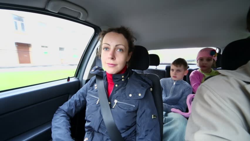 Family of four drive in car, children sit on backseat, (panoramic motion) - HD stock footage clip