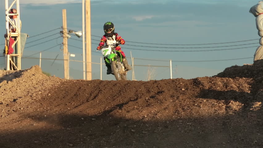 Youth motorcycle race slow motion. Crossing finish line hill. Motocross youth motorcycle race on dirt track. Turns, hills and jumps challenge riders of all ages. - HD stock video clip