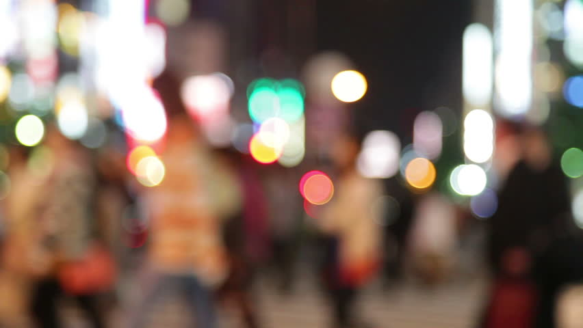 People walking in city night background. Pedestrians walking in city night with lights. Out of focus background from busy big city with people crossing street. Tokyo, Japan.