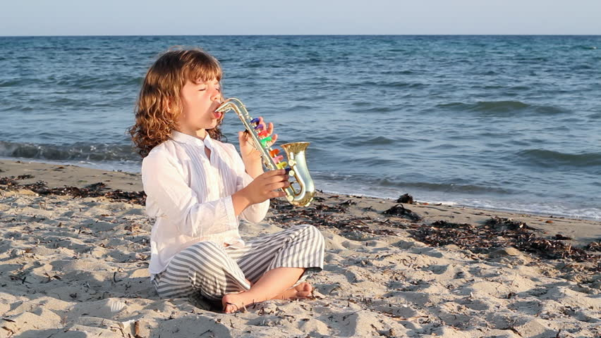 little girl play saxophone on beach - HD stock video clip