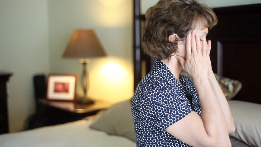 A troubled, stressed out woman sitting on her bed who appears to be suffering from a headache - HD stock video clip