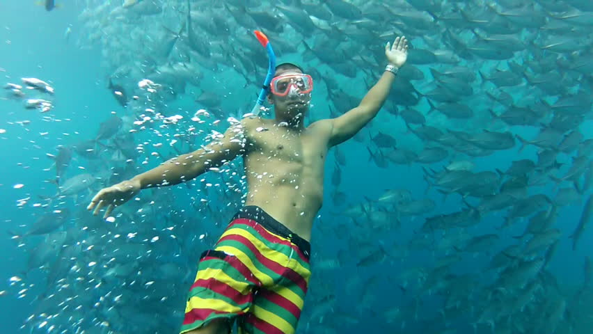 Person swimming among shoal of jack fish in tulemben in Bali, Indonesia