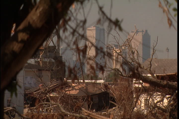 Tree branches hanging in front of view of New Orleans skyscrapers. Camera zooms across rubble pile to skyline in New Orleans after Hurricane Katrina (October 2005).