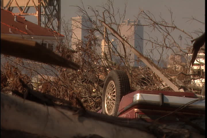 Overturned car in rubble pile in New Orleans after Hurricane Katrina (October 2005). Skyline is visible in background.