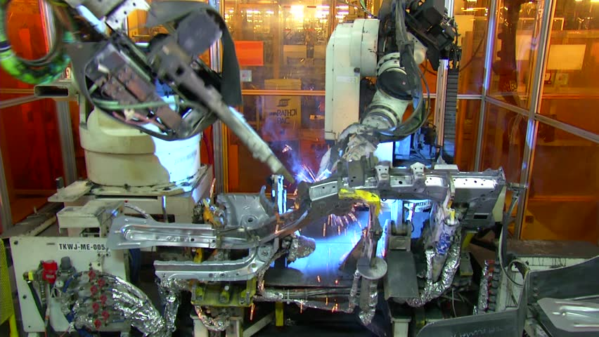 Robots are welding in automobile factory. jib shot.