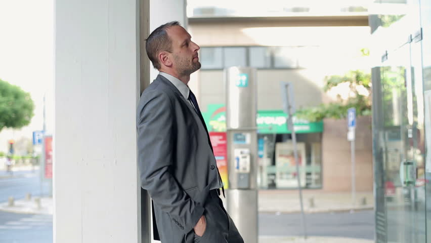 Young businessman waiting for someone in the city  - HD stock footage clip