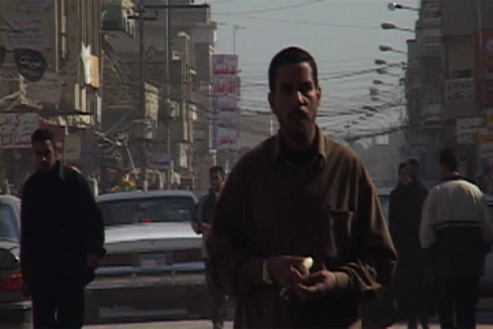 NASIRIYAH, IRAQ - DECEMBER 14, 2003: Camera follows Iraqi man as he walks through busy street past many shops.
