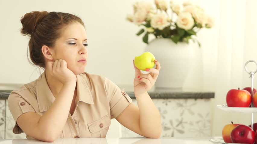 Teenager eating apple and looking at camera with smile
