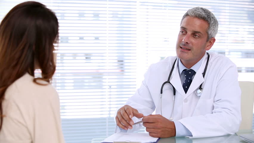 Smiling doctor talking to his female patient - HD stock video clip