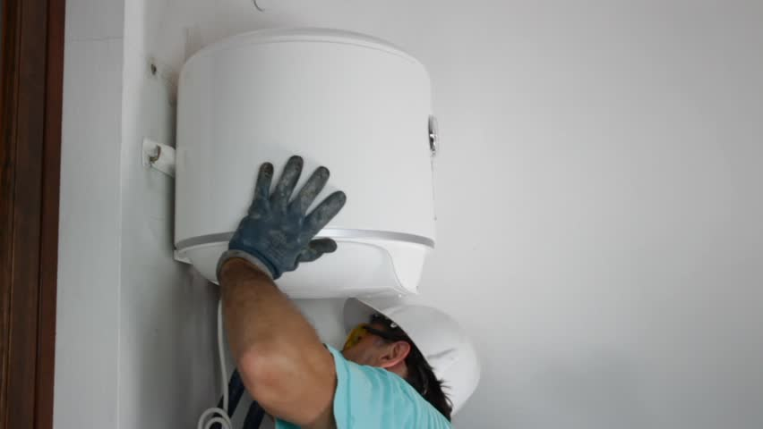 plumber installing an electric water heater - HD stock video clip