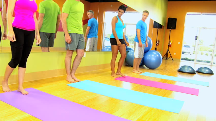 Caucasian female fitness instructor with multi ethnic class using mats for floor exercises - HD stock video clip