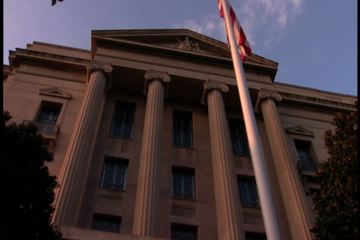 Low angle shot of entrance to Robert F. Kennedy Department of Justice building and flag pole in Washington, D.C..