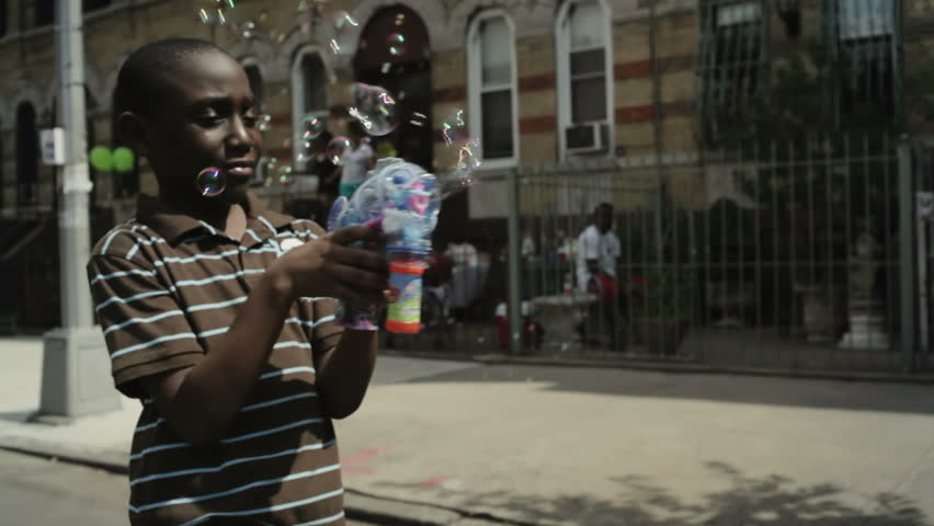 black boy playing with bubble gun in the street at a block party