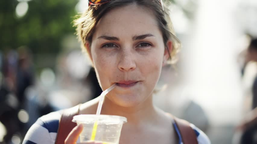 Beautiful woman portrait in city looking at camera sipping juice - HD stock video clip