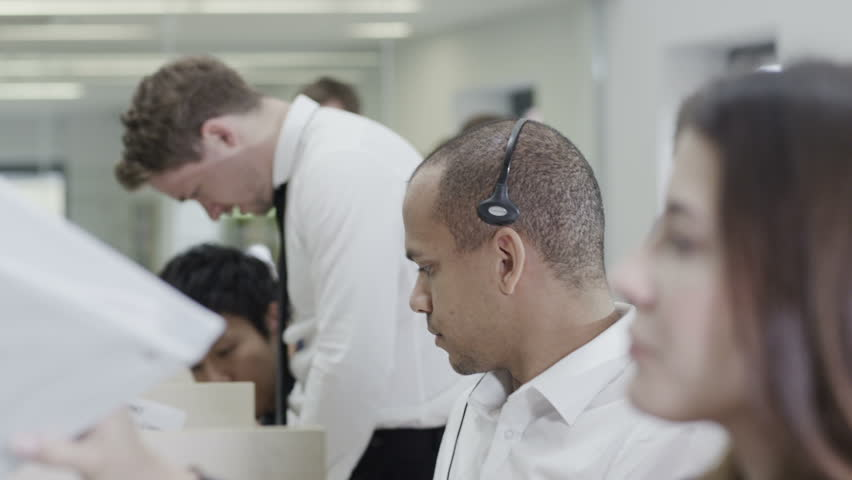 Cheerful young customer service operator, at work in a busy call center