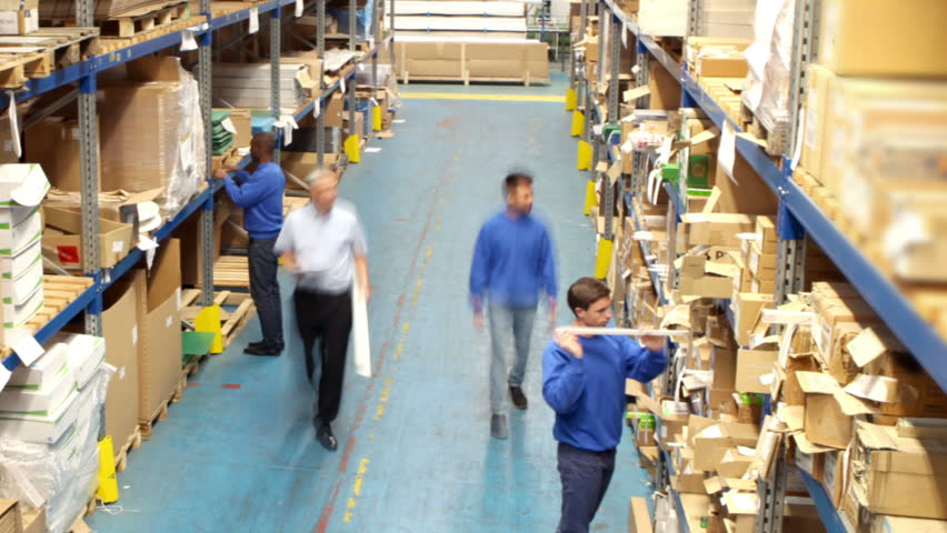 Time lapse of a busy group of workers in a warehouse or factory preparing goods for dispatch.