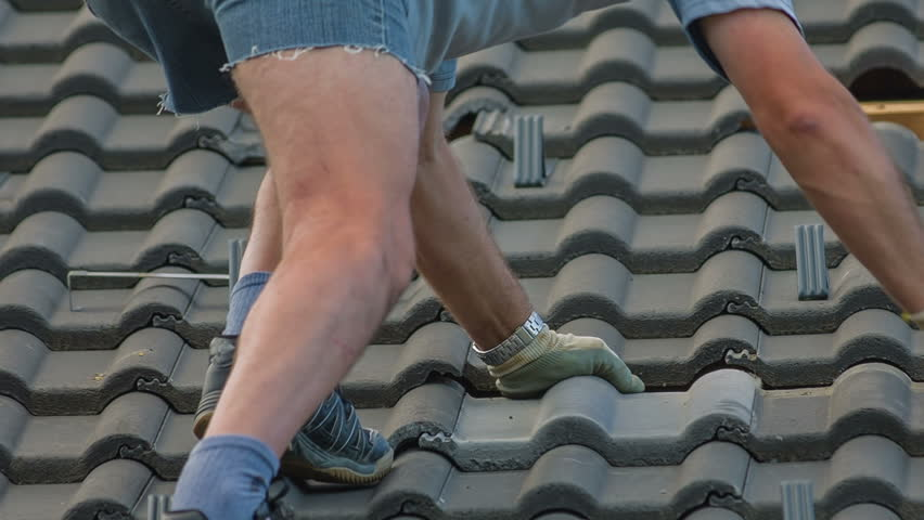 Fixing Roof Tiles After Hail Storm Close Up. Destroyed roof tiles on completely new house with no facade and no insurance yet. Man changes broken tiles because of hail storm destroyed the roof. - HD stock footage clip