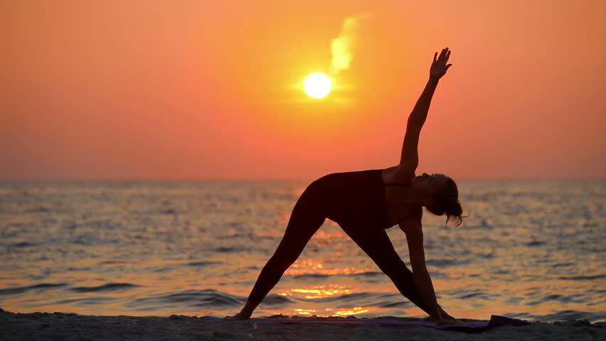 a young woman with a slender figure is engaged in gymnastics at sea at sunrise