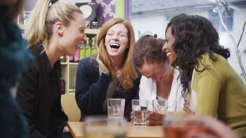 Happy and attractive group of female friends chatting and laughing together in a small cafe or wine bar. - HD stock footage clip