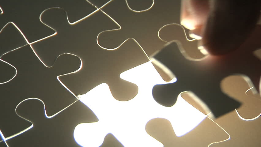 Hand places piece into puzzle