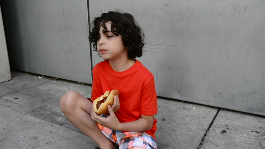 Young child eating hot dog outside the Eaton Centre in downtown Toronto. Latin boy taking a break and having a snack while his father takes pictures. Eating a hot doy in the street