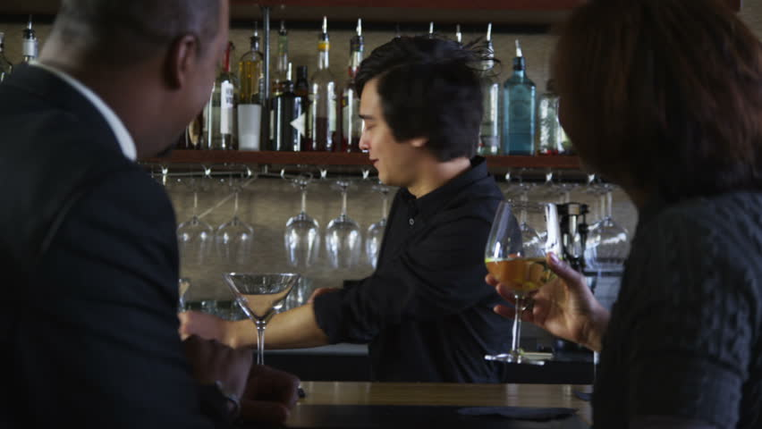 Bartender talks to customers and serves drinks - HD stock footage clip