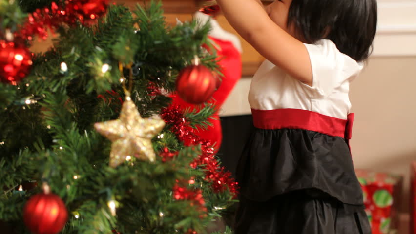 Young girl putting ornament on Christmas tree