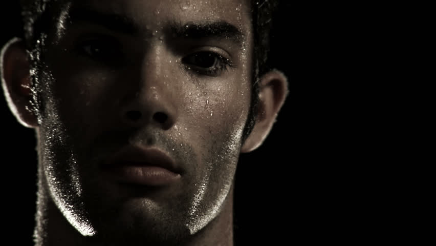 Male Athlete dripping with sweat turns and stares at the camera.