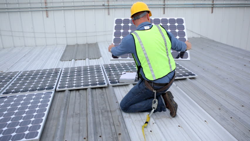 Contractor installing solar panels on rooftop - HD stock video clip