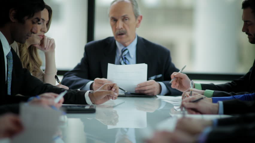 An older businessman leads a meeting at a large table and reads from his paper