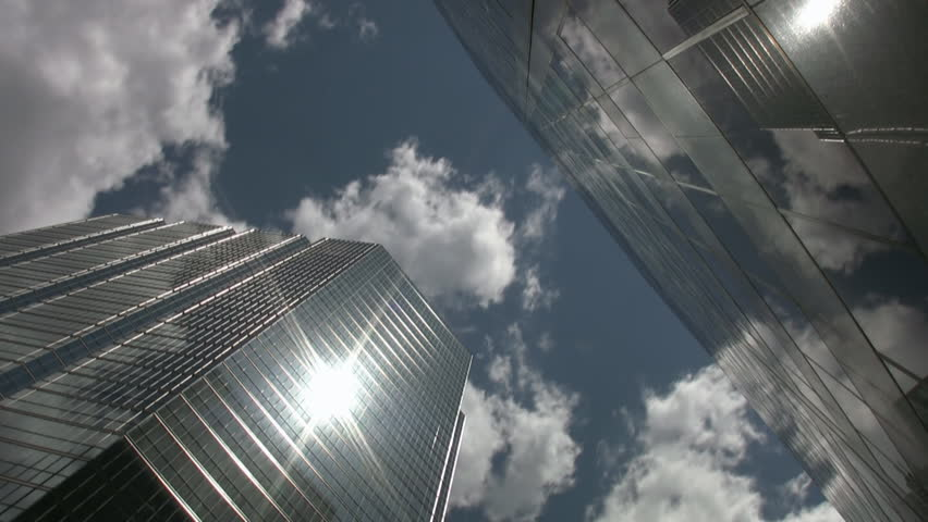 Office towers reflect sun and clouds. Timelapse shot.