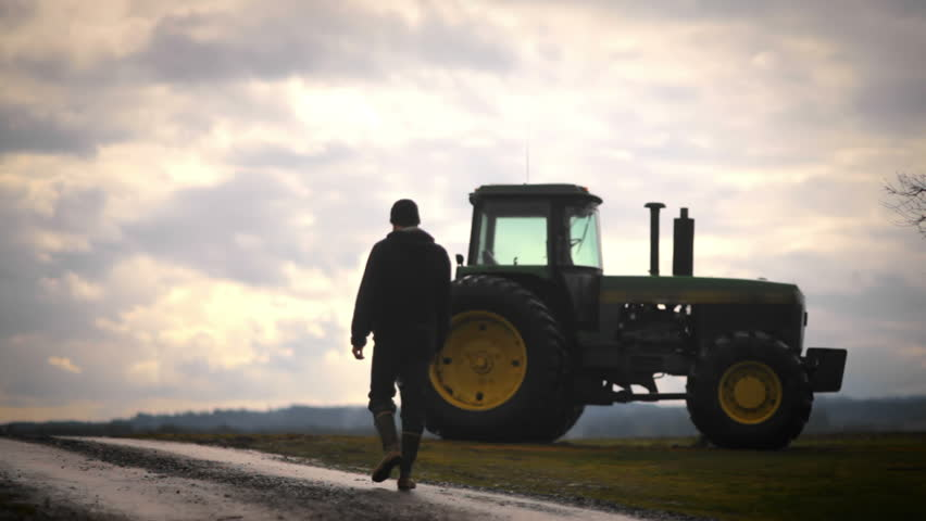 A farmer walks towards his tractor in the early morning while silhouetted