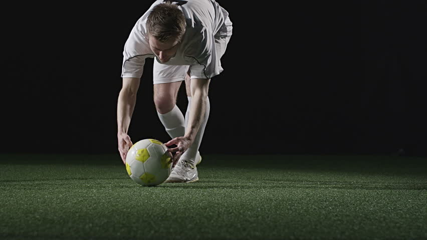 A soccer player sets up a penalty kick and then kicks the ball. Medium slow motion shot.