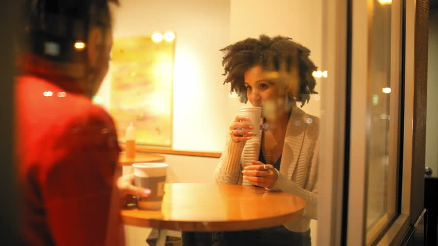 Two attractive young friends have a conversation together over a cup of coffee. Medium shot. - HD stock video clip
