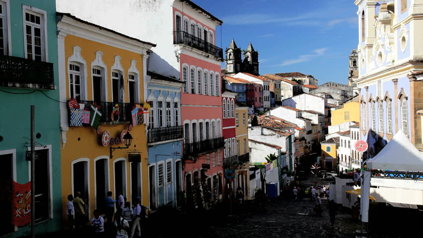 Street level view of pedestrian activity in a cobblestone alley in front of beautiful colorful buildings in Pelourinho, old Salvador, Brazil